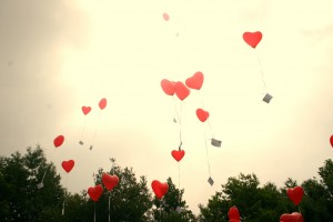 Heart balloons with messages floating into the sky